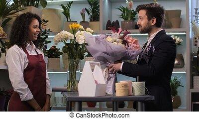 Happy florist giving floral arrangement to client - Side...