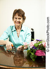 Happy Florist - Happy woman in wheelchair, arranging a...