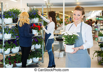 Happy Florist Holding Flower Pot In Shop