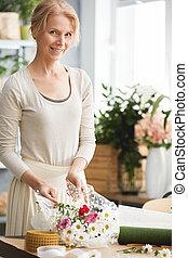 Happy florist in flower studio