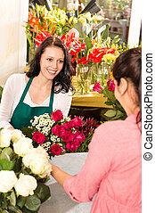 Happy florist making roses bouquet women customer