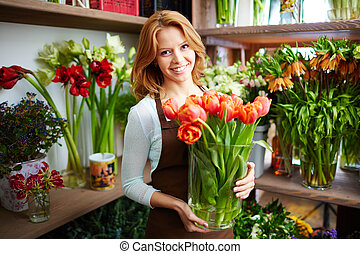 Portrait of young female florist with big vase of red tulips looking at camera