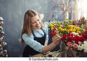happy florist putting fresh mimosas in water