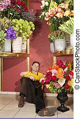 Happy florist resting in his shop