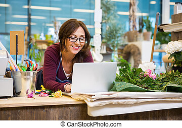 Happy Florist Using Laptop At Counter In Flower Shop - Happy...