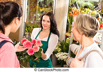 Happy florist woman showing roses flowers customers