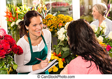 Happy florist writing flower shop talking customer woman
