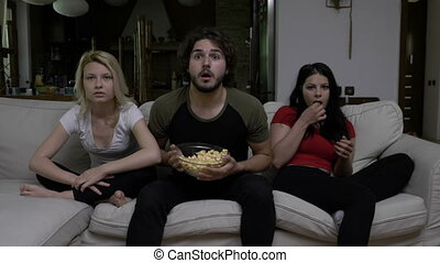 Happy football fans watching game and supporting favorite team while eating popcorn in living room