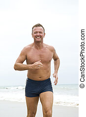 happy forties man jogging on beach.