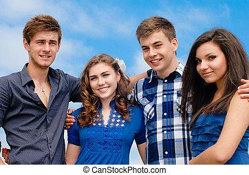 Happy four teenage friends hugging