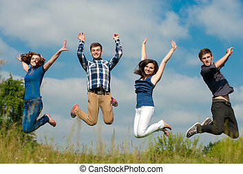 Happy four teenage friends jumping