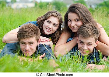 Happy four teenage friends lying in grass