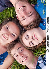Happy four teenage friends lying in grass