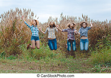 Happy four teenage girls jumping and holding hands in countryside