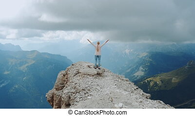 Happy free woman with outstretched hands on the top on the rock. Enjoying nature and feeling free.