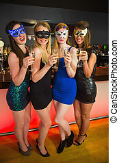 Happy friend with masks on holding champagne smiling at...