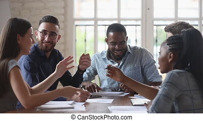 Happy friendly diverse startup team people talking laughing working together