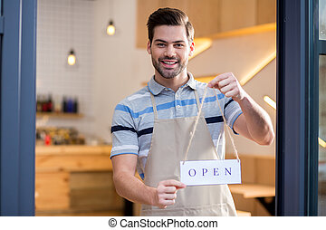 Happy friendly man inviting to his cafe