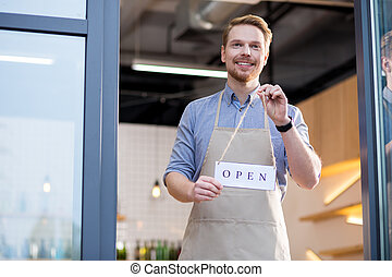 Happy friendly waiter inviting customers