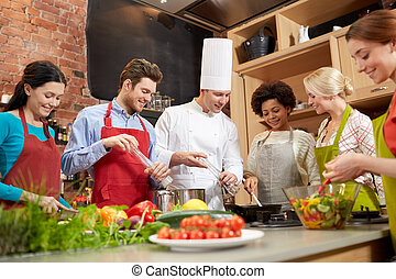 happy friends and chef cook cooking in kitchen - cooking ...