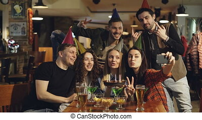 Happy friends are making selfie with birthday cake using smart phone while celebrating in cafe. Young people are having fun, making silly faces and laughing.