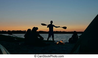 Happy friends are singing and playing the guitar getting warm around fire in forest near river on summer night.