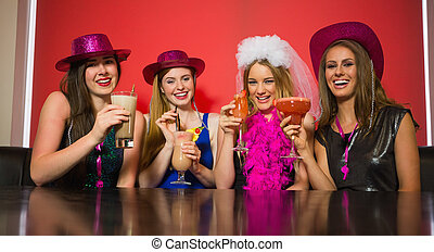 Happy friends at a hen night drinking cocktails