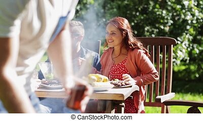 happy friends at barbecue party in summer garden