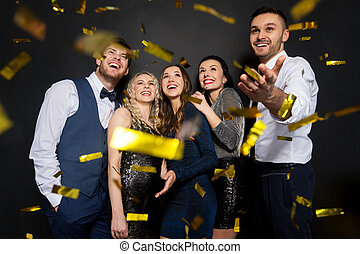 happy friends at party under confetti over black