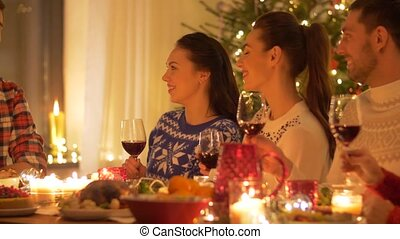 happy friends celebrating christmas at home - holidays and...