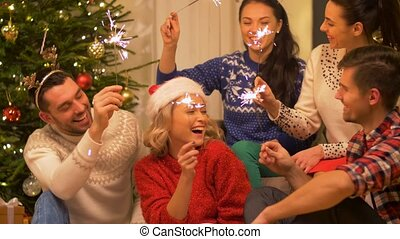 happy friends celebrating christmas at home party