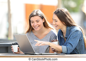 Happy friends checking online content on laptop in a park