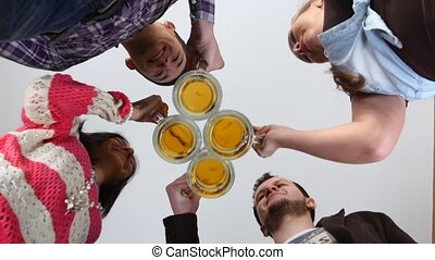 Happy friends clinking beer glasses. A bottom plan view.