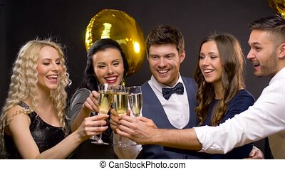 happy friends clinking champagne glasses at party -...