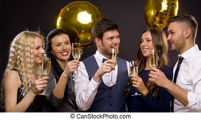 happy friends clinking champagne glasses at party