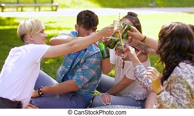 happy friends clinking drinks at summer park