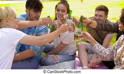 happy friends clinking drinks at summer park - leisure,...