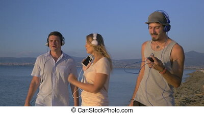 Happy friends dancing with music at the seaside - Steadicam...