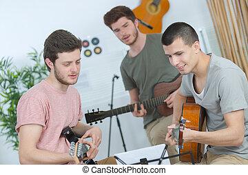 happy friends doing a guitar trio
