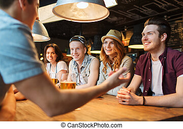 happy friends drinking beer and talking at bar