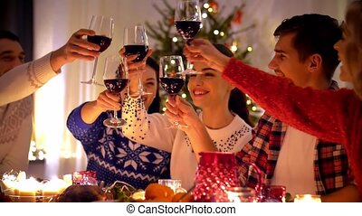 happy friends drinking red wine at christmas dinner -...
