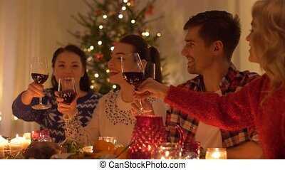 happy friends drinking red wine at christmas - holidays and...