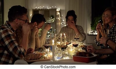 happy friends drinking red wine at christmas party - ...