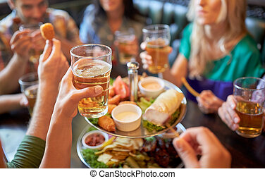 happy friends eating and drinking at bar or pub - leisure, ...