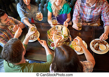 leisure, food, drinks, people and holidays concept - happy friends eating snack and drinking beer at bar or pub