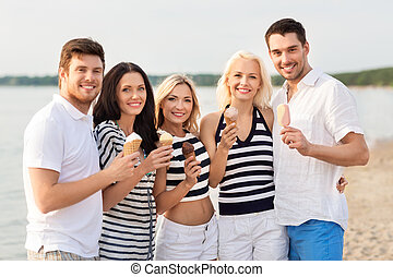 happy friends eating ice cream on beach