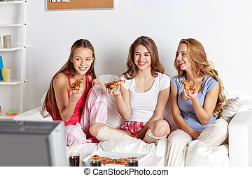 happy friends eating pizza and watching tv at home -...