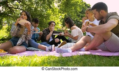 happy friends eating sandwiches at summer picnic -...