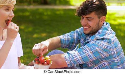 happy friends eating strawberries at summer picnic -...