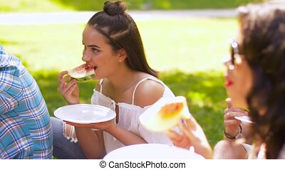happy friends eating watermelon at summer picnic -...